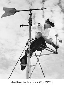 Low angle view of a young woman mending a weather vane