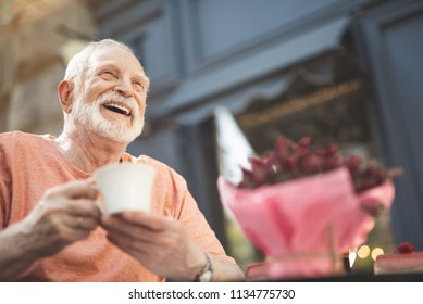 Low angle waist up portrait of delighted mature male sitting at table outside. He is holding cup of hot drink and looking with pleasure and content. Copy space in right side