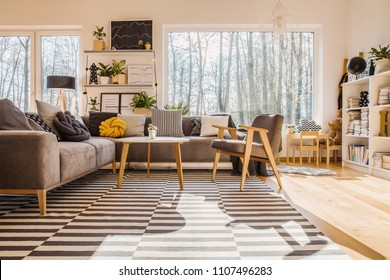 Low angle of warm bright living room interior with armchair at wooden table next to corner sofa