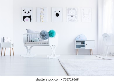 Low angle of white cradle with pompons in baby's room with animal pictures on wall