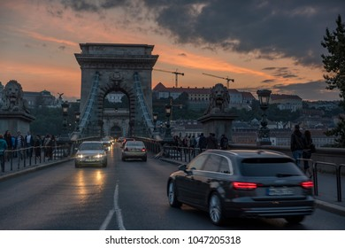 Low angle wide shot of traffic crossing the Chain Bridge in Budapest. Taken at dusk looking towards Budpa Castle