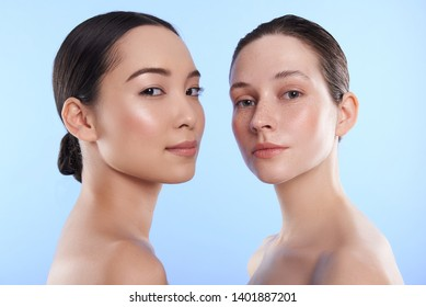 Low angle of young charming Asian and Caucasian ladies with different types of skin standing opposite and looking at camera in studio. Beauty, facial treatment and spa concept