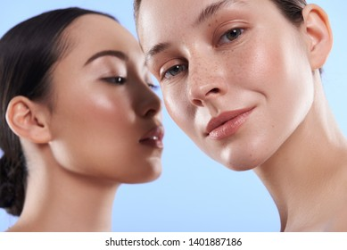 Low angle of young pretty Asian and Caucasian ladies with different types of skin standing near each other and looking at camera in studio. Beauty, facial treatment and spa concept