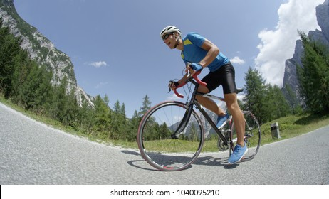 LOW ANGLE: Young pro biking athlete training hard in nature on advanced road bicycle. Active Caucasian biker yells in exhaustion during difficult stage of bicycle race over picturesque mountain pass.
