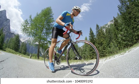 LOW ANGLE: Young pro road cyclist training intensely for race in the sunny mountains. Athletic man wearing sunglasses riding his bike on asphalt road on a lovely spring day in beautiful countryside.