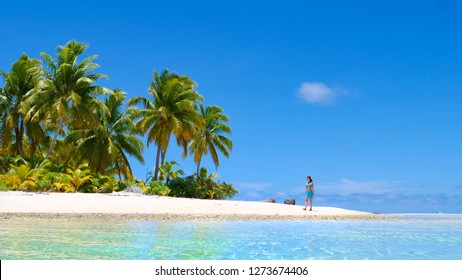 6ed9e8cf04e6 LOW ANGLE  Young woman in bikini walking along the untouched exotic  shoreline with hot white