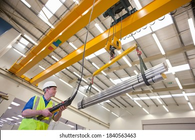 Low angled shot of a technician wearing a helmet while operating hoist with raw aluminum in a hi-tech manufacturing plant.