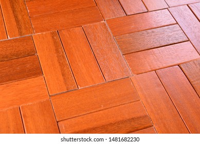 Low angled view of hardwood flooring in a parquet pattern with light reflections can be used as a background or color sample.  Stained and varnished in a medium red brown mahogany tone.