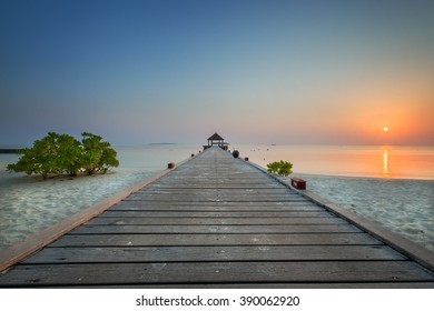 Low angled view out to sea along the jetty boardwalk at Komandoo Island resort in the Maldives at sunrise.
