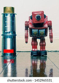 low battary concept with old tin cans and a retro robot on a wooden floor with reflection
