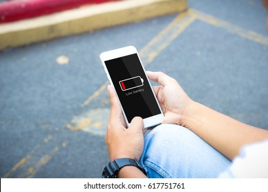 Low battery concept.Man hands holding mobile phone