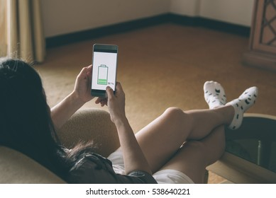 Low battery concept. young woman holding a smart phone with low battery on screen.