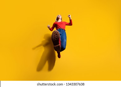 Low below angle full length body size view of her she nice fit thin slim attractive cheerful cheery girl having fun going making step isolated over bright vivid shine orange background