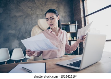 Low below angle view photo of entrepreneur sad upset unhappy comparing accounting paper of two periods sitting before laptop on desktop frowing with misunderstanding