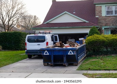 Low blue dumpster full of cardboard and construction debris in front of a full garage and next to a white worker's van