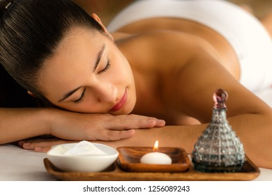 Low candle light portrait of woman relaxing in spa next to massage oil and beauty product.