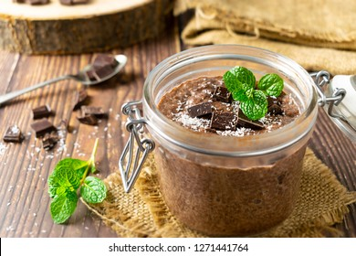 Low Carb Chocolate Chia Pudding in a glass jar on wooden table with pieces of chocolate, flaked coconut and mint leaves. Food photography