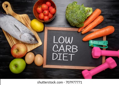Low carb diet on chalkboard, health conceptual. Healthy fresh low carbohydrates food; egg, fish, lemon, tomatoes, apple, carrot and broccoli with dumbbell and measuring tape.