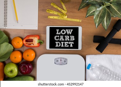 LOW CARB DIET top view, digital tablet on a wooden table,  fitness and weight loss concept, dumbbells, white scale, towels, fruit, Weight loss
