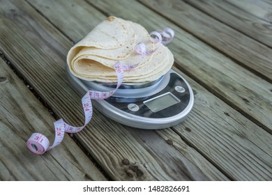 Low carb tortillas on a food scale with measuring tape on wooden background. Blank empty room for text or copy space. Healthy health food trend for keto and low-carb diets. Plain tortilla, high fiber.