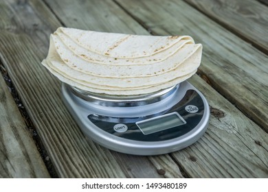 Low carb tortillas on a scale on wooden background - blank empty room for text or copy space. A tortilla low in carbohydrates that fits into the keto diet - a new health food trend. Plain tortillas.
