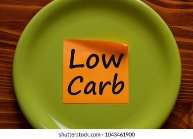 Low carb written in orange sticky note on the green plate.Business concept.Top view.