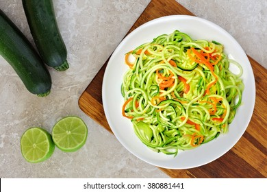 Low carb zucchini noodle dish with carrots and lime on white marble background, overhead view