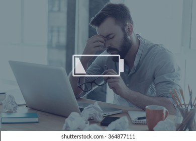 Low charge. Digitally composed symbol of law charged battery over a picture of frustrated young man touching his forehead and keeping eyes closed