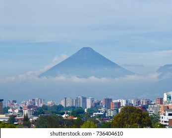 A low cloud base covers part of Fuego volcano in Guatemala City, capital of Guatemala. City skyline is in the foreground.