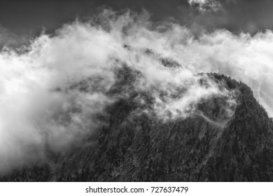 Low clouds hang over rugged cliffs in the Wasatch mountains in Utah
