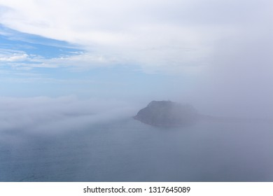 Low clouds and mist over ocean concealing a small island - mystical landscape