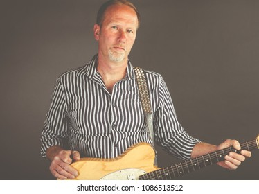 Low contrast faded portrait of a middle aged musician holding an electric guitar with desaturated film look