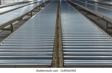 Low, converging perspective of industrial steel roller conveyors.