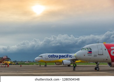 Low cost airlines Cebu Pacific and Air Asia aircraft at colorful sunset at Puerta Princesa Airport in Palawan island, Philippines. August 2018.