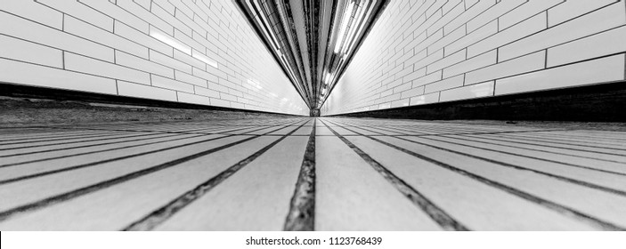low down view of a tunnel with leading lines and vanishing point tiles on the floor and tunnel on black and white
