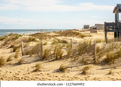 Low dunes with sand fences and patchy grass near beach houses in the Outer Banks of North Carolina, USA, for coastal and environmental themes