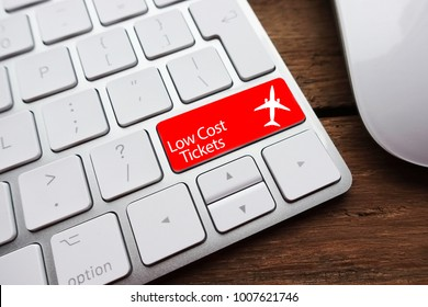 Low fare or cheap flights concept suggested by white computer keyboard with low cost tickets text on red enter key