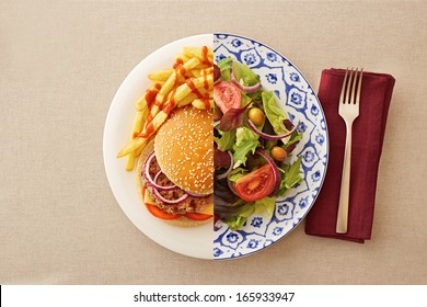 Low fat healthy salad against unhealthy greasy burger
