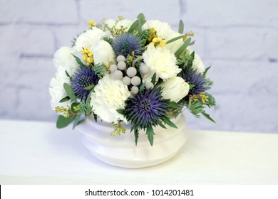 Low flower arrangement on the chest of drawers