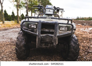 Low front bumper view of a muddy 4-wheel all terrain vehicle