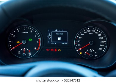 Low Fuel sign and additional instruments on car dashboard.