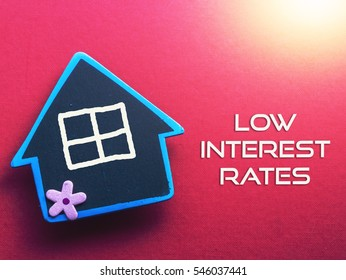 LOW INTEREST RATE written on red background with wooden house
