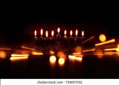 Low key abstract image of jewish holiday Hanukkah background with menorah (traditional candelabra) and burning candles.