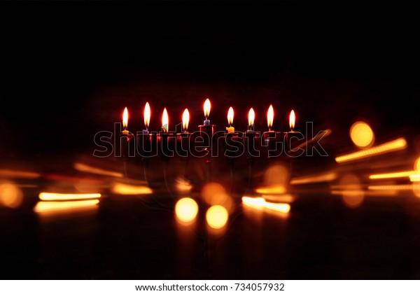 Imagen abstracta de bajo nivel de yeguas de fondo de Hanukkah con menorah (tradicional candelabra) y velas ardiendo.