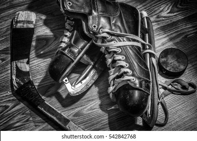 low key black and white horizontal image of a pair of old antique men's skates lying on the floor with a hockey stick and puck beside it.