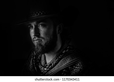 Low key, black and white male cowboy in a poncho portrait