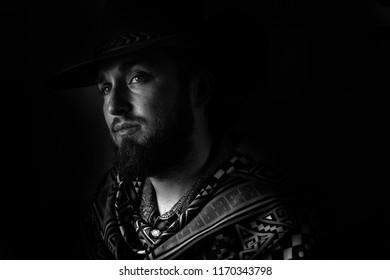 Low key, black and white male cowboy in a poncho portrait