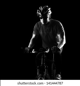 low key black and white silhouette of a cycling man black background