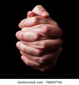 Low key, close up of hands of a faithful mature man praying, hands folded, interlaced fingers in worship to god. Isolated black background. Concept for religion, faith, prayer and spirituality.