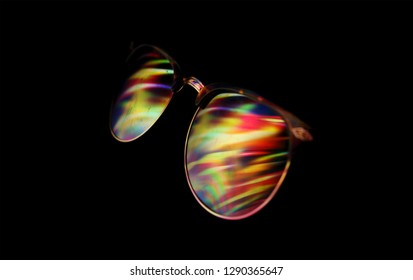 Low key, close up sunglasses in the night relecting the rainbow lights of a colorful vortex, illustrating movement, hypnosis, screen addictions...